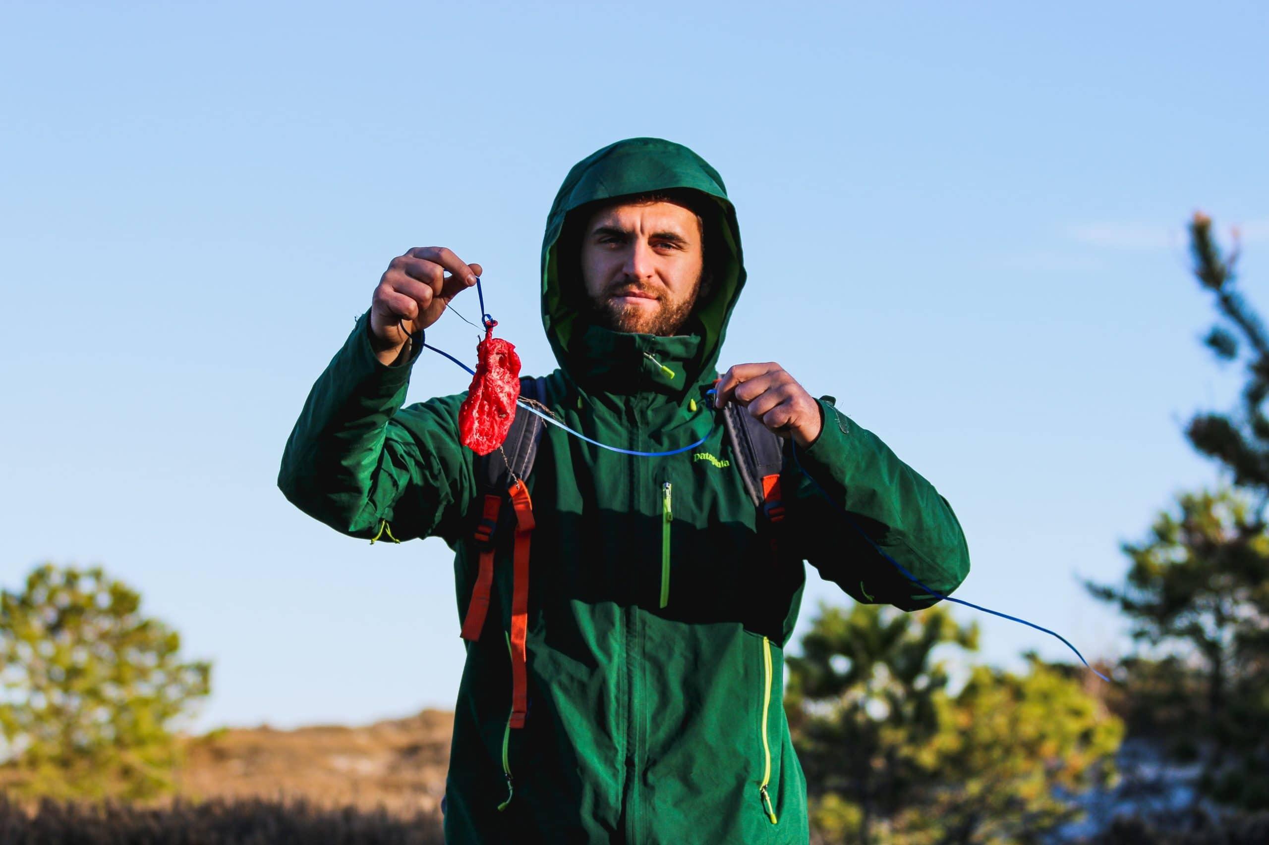 A man holds up a littered balloon