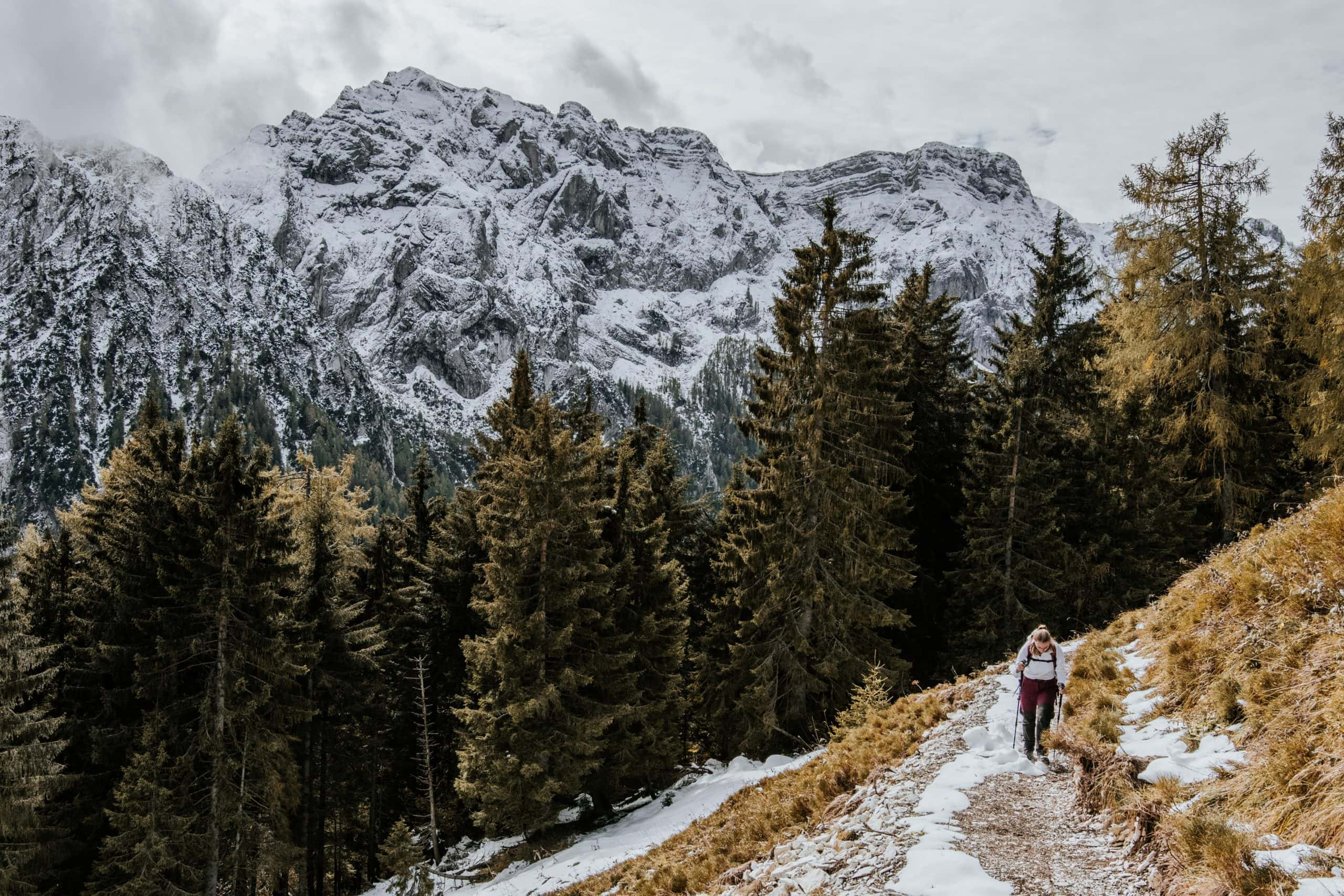 A person hikes on a snowy trail with snowy mountains in the background